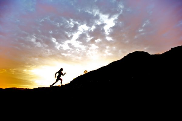 Runner in silhouette against rising sun, running uphill